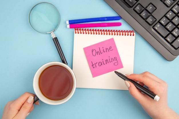 Widok z góry na szkolenie online napisane na filiżance herbaty i markera w kobiecych rękach klawiatura lupa notatnik niebieskie i różowe markery na niebiesko