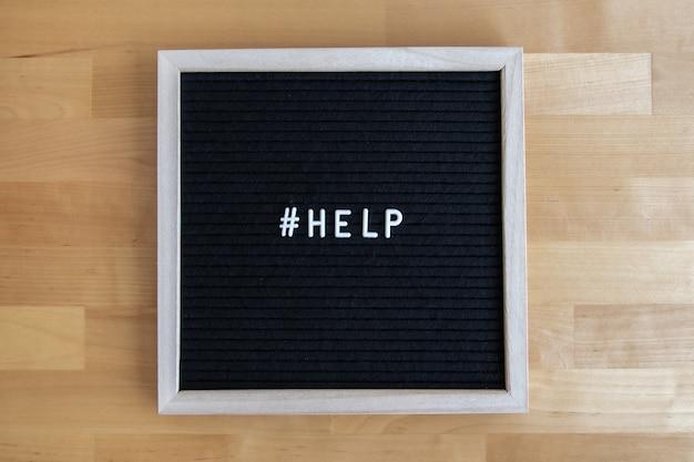 Widok z góry na tablicę z cytatem pomocy na drewnianym stole