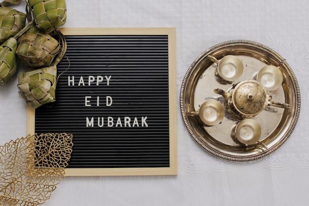 Widok z góry na tablicę z literami mówi happy eid mubarak i tradycyjne jedzenie podczas lebaran celebracji zwanej ketupat ze złotym czajniczkiem i filiżankami