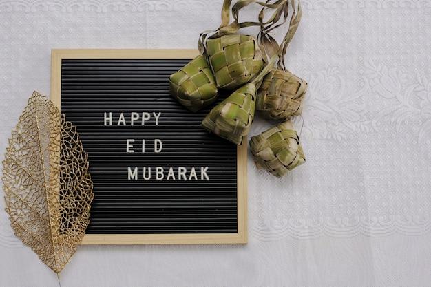 Widok z góry na tablicę z literami mówi happy eid mubarak i tradycyjne jedzenie podczas lebaran celebracji zwanej ketupat