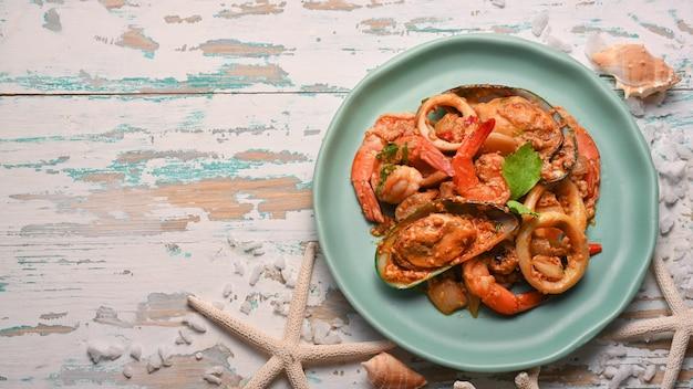 Widok z góry na tajskie jedzenie, owoce morza w proszku curry smażone na zielonym talerzu ceramicznym na drewnianym stole