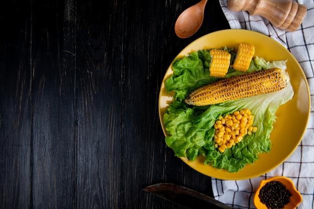 Widok z góry na talerz całych i pokrojonych kukurydzy z nasionami kukurydzy i sałatą z nożem na szmatce i czarnym z miejsca na kopię