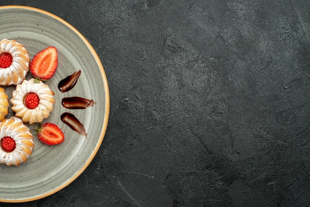 Widok z góry na talerz ciastek talerz apetycznych ciastek z czekoladą i truskawką po lewej stronie stołu