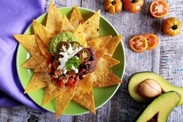 Widok z góry na talerz domowych chipsów kukurydzianych zwieńczonych wegetariańskim chili fasolowym, mozarellą i jalapenos przy drewnianym stole