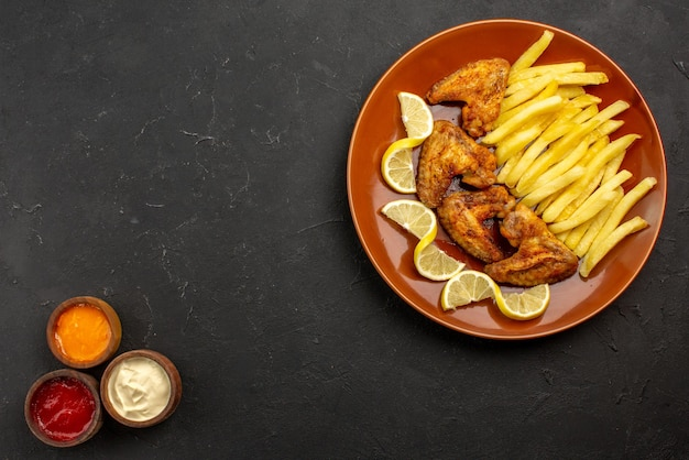 Widok z góry na talerz fastfood z apetycznymi skrzydełkami z kurczaka, frytkami i cytryną po prawej stronie i trzema rodzajami sosów po lewej stronie stołu