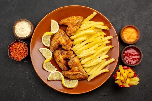 Widok z góry na talerz i sosy pomarańczowy talerz skrzydełek z kurczaka i frytek między trzema rodzajami sosów i kolorowych przypraw na środku stołu
