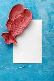 Widok z góry na talerz w kształcie homara z papierem