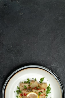 Widok z góry na talerz z apetycznym daniem apetyczne danie z gołąbkami z cytryną i sosem na białym talerzu na czarnej powierzchni