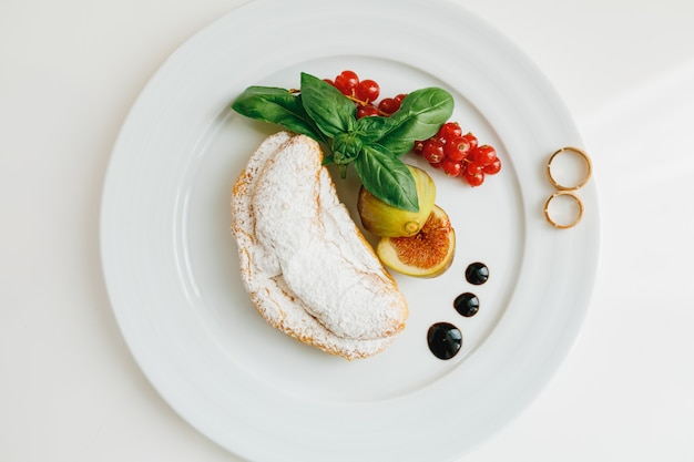 Widok z góry na talerz z dwiema złotymi obrączkami, rogalik z cukrem pudrem i figami i