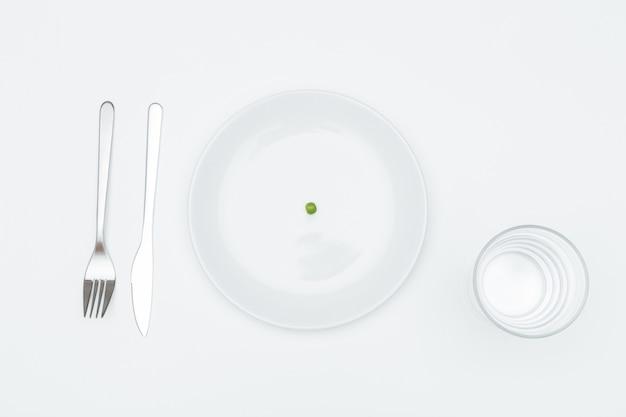 Widok z góry na talerz z jednym groszkiem, szklanką wody? widelec i nóż