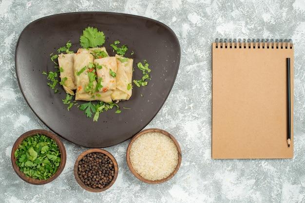 Widok z góry na talerz z jedzeniem talerz nadziewanej kapusty i talerze z czarnym papierem ryżowym i ziołami po lewej stronie stołu obok kremowego notatnika z ołówkiem