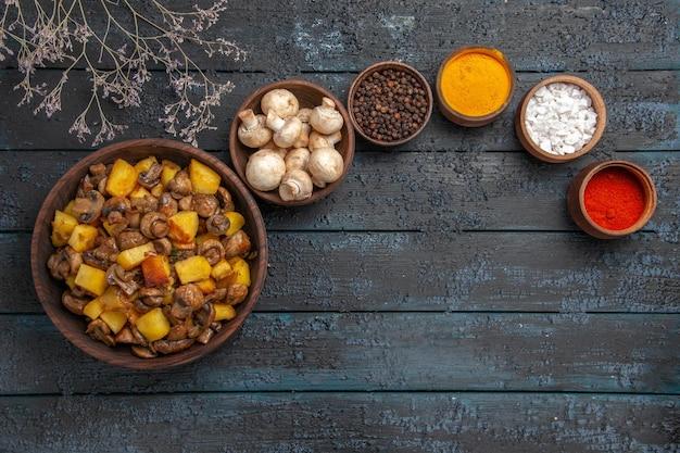 Widok z góry na talerz z jedzeniem z grzybami i ziemniakami obok białych grzybów i kolorowych przypraw