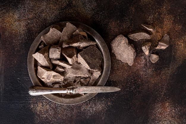 Widok z góry na talerz z kawałkami czekolady i nożem