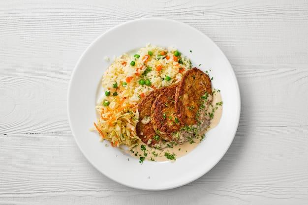 Widok z góry na talerz z kotletem z wątróbki, ryżem z groszkiem i marynowaną kapustą