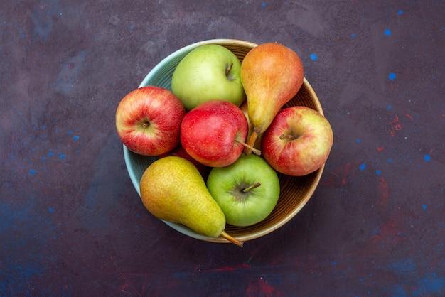 Widok z góry na talerz z owocami, gruszkami i jabłkami na ciemnej powierzchni