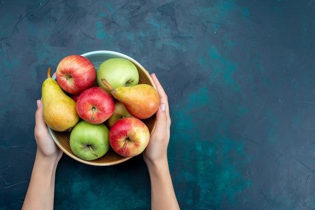 Widok z góry na talerz z owocami, gruszkami i jabłkami na ciemnoniebieskim biurku