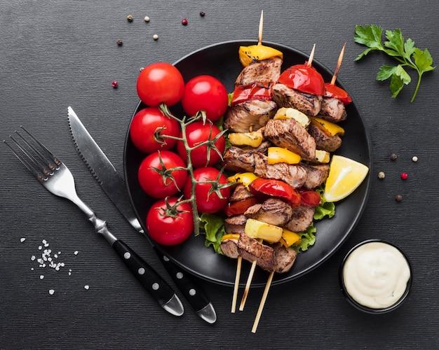Widok z góry na talerz z pysznym kebabem i pomidorami