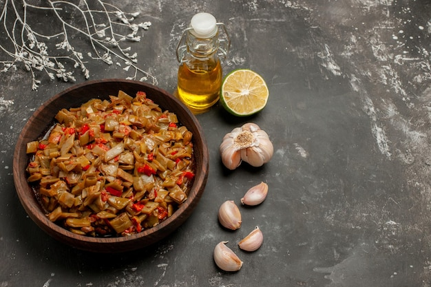 Widok z góry na talerz zielonej fasoli butelka oleju z cytryną i czosnkiem obok talerza zielonej fasoli z pomidorami i gałęziami drzew na ciemnym stole