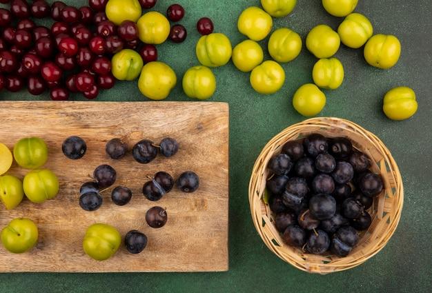 Widok z góry na tarniny z zielonymi śliwkami wiśniowymi na drewnianej desce kuchennej z czerwonymi wiśniami i zielonymi śliwkami wiśni na białym tle na zielonym tle