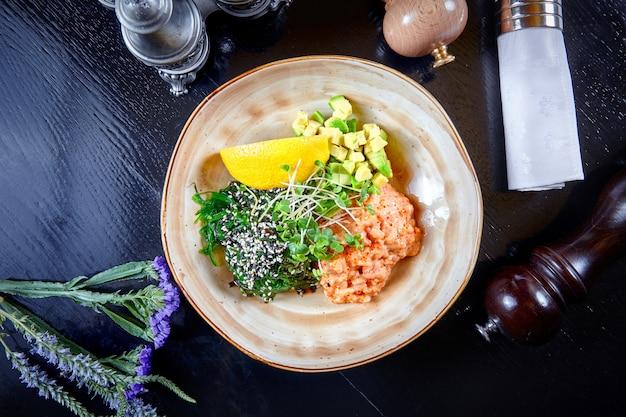 Widok z góry na tatar z łososia z awokado, cytryną, mikrogreenem w białej muszce na ciemnym tle. skopiuj miejsce owoce morza. zdrowe jedzenie na lunch. posiłek dla smakoszy. surowa mączka rybna