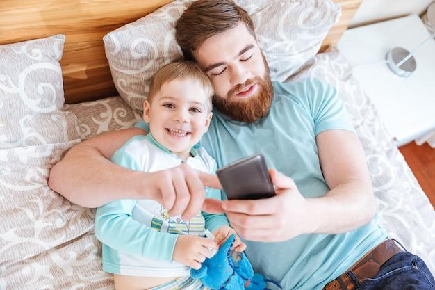 Widok z góry na tatę i syna leżących na łóżku i używających razem telefonu komórkowego