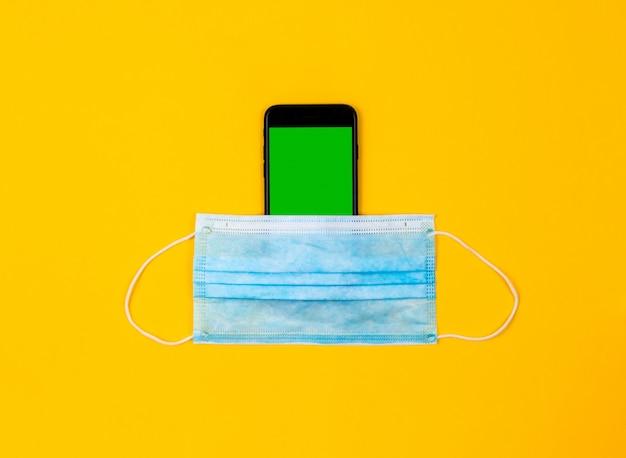 Widok z góry na telefon komórkowy, który leży na żółtym tle i ma na sobie maskę medyczną. pojęcie ochrony i środków ostrożności przeciwko wirusowi koronawirusa. chromowanie i makieta zielonego ekranu