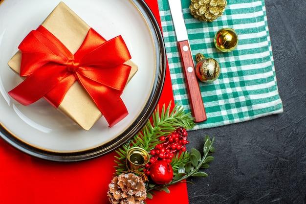 Widok z góry na tło krajowego posiłku świątecznego z prezentem z czerwoną wstążką w kształcie łuku na pustych talerzach zestaw sztućców akcesoria do dekoracji na zielonym ręczniku w paski