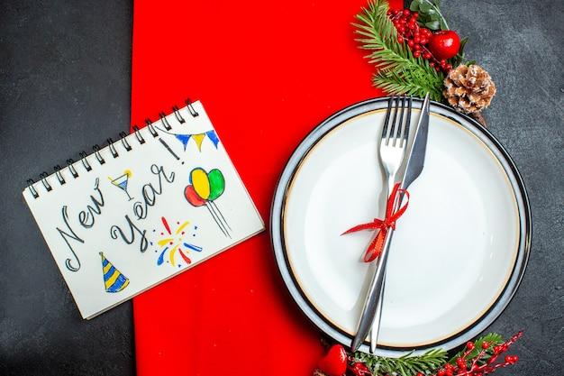 Widok z góry na tło nowego roku z zestawem sztućców z czerwoną wstążką na obiadowym talerzu akcesoria do dekoracji gałęzi jodły obok notatnika z piórem na czerwonej serwetce