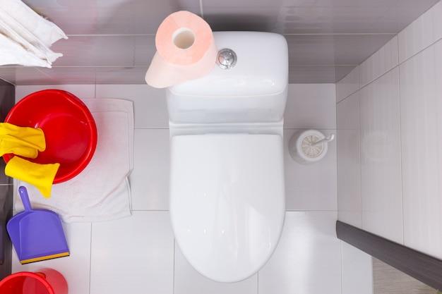 Widok z góry na toaletę z kolorowym zestawem różnorodnych domowych środków czystości i rolką miękkiego różowego papieru toaletowego