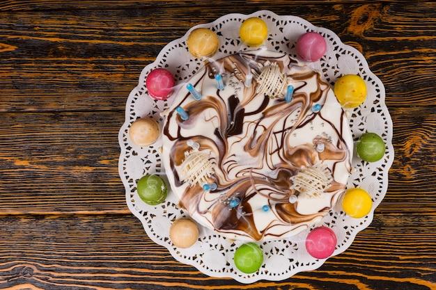 Widok z góry na tort urodzinowy z dużą ilością świec w pobliżu różnych kolorowych makaroników, na drewnianym biurku