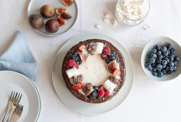 Widok z góry na tort z jagodami i czekoladą na białym obrusie tortu urodzinowego