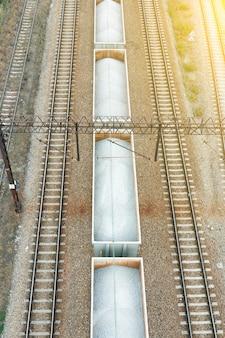 Widok z góry na tory kolejowe z wagonami z kamieniem w letni dzień
