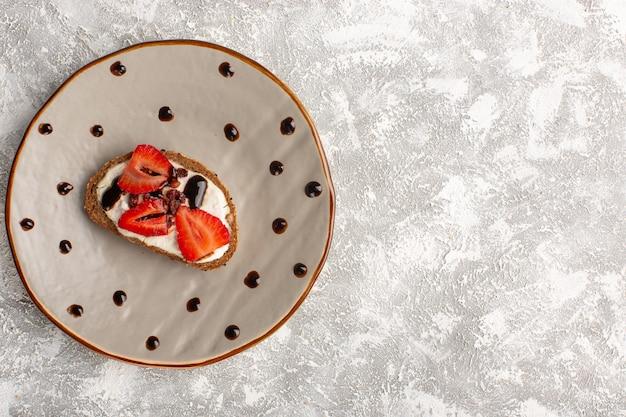 Widok z góry na tosty z truskawkami i kwaśną śmietaną wewnątrz brązowego talerza na szarej jasnej powierzchni
