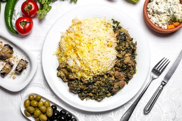 Widok z góry na tradycyjne danie z azerbejdżanu smażone mięso pilaw syabzi z zieleniną i gotowanym ryżem