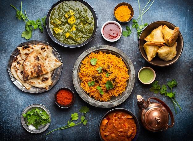 Widok z góry na tradycyjne indyjskie potrawy i przekąski: curry z kurczaka, pilaw, chleb naan, samosy, paneer, chutney na tle rustykalnym. stół z wyborem dań kuchni indyjskiej, kolacja/bufet