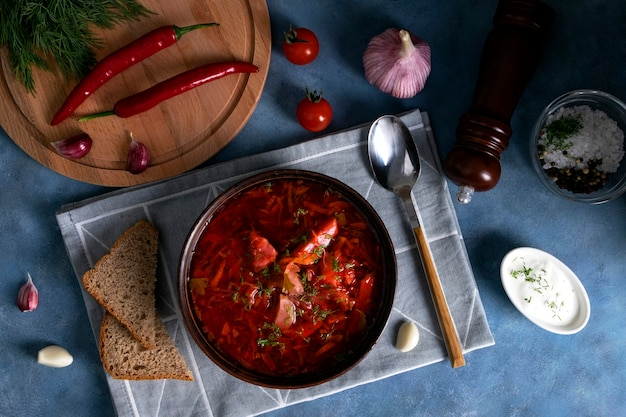 Widok z góry na tradycyjny popularny rosyjski barszcz zupowy z kapusty, buraków i innych warzyw podawany w glinianym talerzu ceramicznym z kwaśną śmietaną i czosnkiem. kuchnia narodowa. selektywne skupienie.