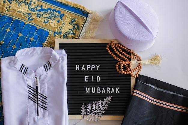 Widok z góry na tradycyjny strój muzułmański i koraliki modlitewne na macie modlitewnej z tablicą z literami mówi happy eid mubarak