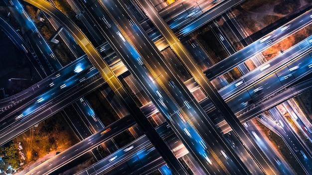 Widok z góry na transport samochodowy na skrzyżowaniu wielopasmowej autostrady lub drogi ekspresowej w mieście azjatyckim w nocy