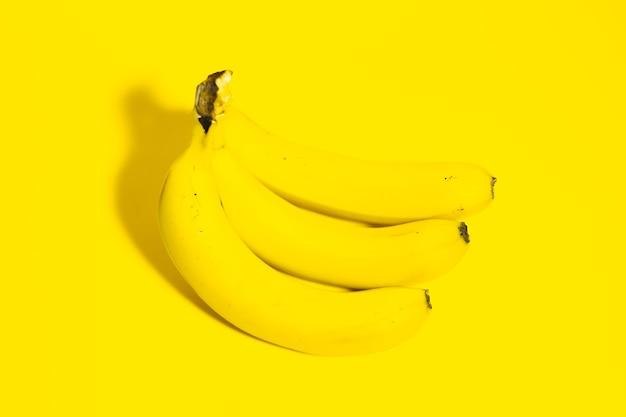 Widok z góry na trzy banany na żółtej powierzchni.