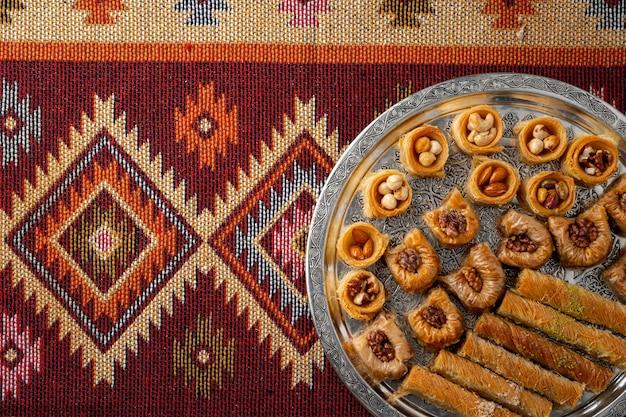 Widok z góry na tureckie desery na tle orientalnego wzorzystego dywanu
