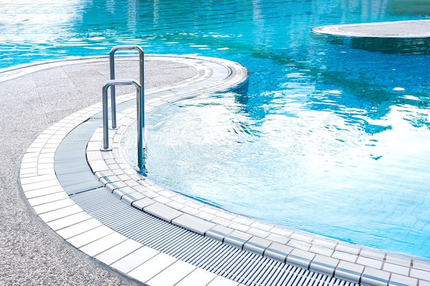 Widok z góry na turkusowy basen z poręczami i schodami. pojęcie lato, relaks, spa, park wodny, architektura.