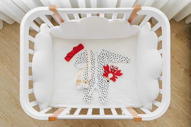 Widok z góry na ubrania i akcesoria dla dzieci w łóżeczku, kołysce. drewniana kołyska dla noworodka w pokoju dziecka.