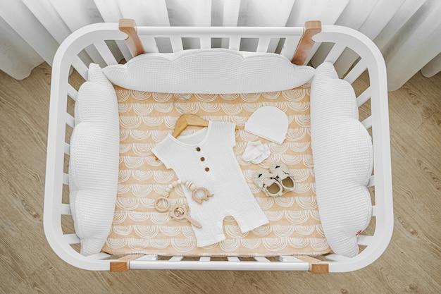 Widok z góry na ubrania i akcesoria dla dzieci w łóżeczku, kołysce. drewniana kołyska dla noworodka z białymi poduszkami w pokoju dziecka.