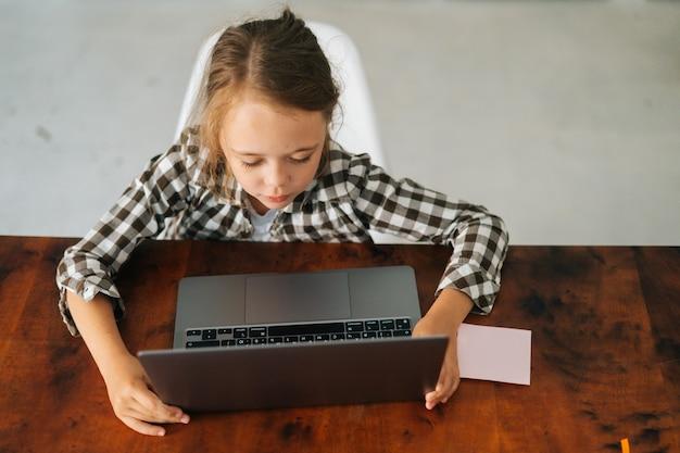 Widok z góry na uczennicę z pokolenia z zaangażowaną w naukę w domu, oglądającą wykład online na temat nauki