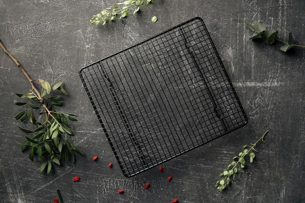 Widok z góry na udekorowane szare tło betonowe z czarną siatką na ciasto