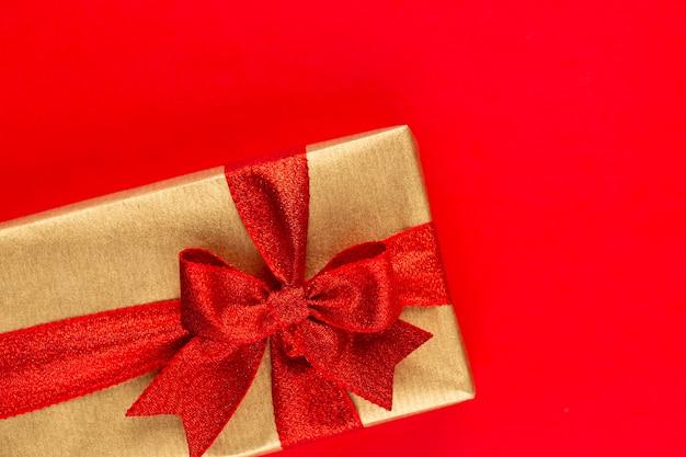 Widok z góry na ułożone zapakowane pudełka na prezenty świąteczne z wstążkami na czerwonym blacie.