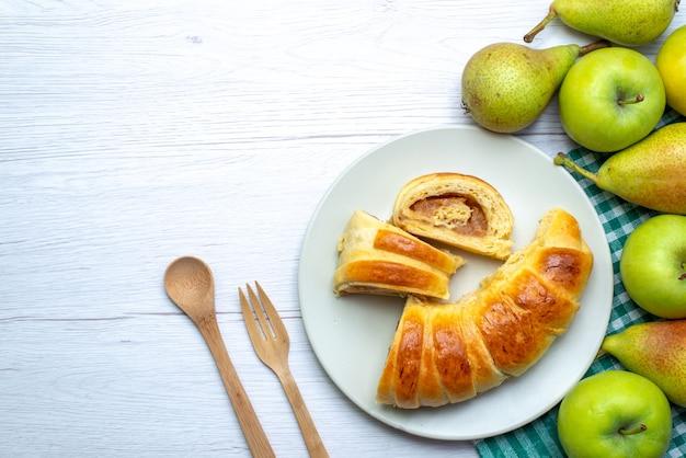Widok z góry na upieczoną bransoletkę z pysznego ciasta uformowaną wewnątrz szklanego pokrojonego talerza wraz z jabłkami i gruszkami na białym biurku, ciastko biszkoptowe słodkie ciasteczko
