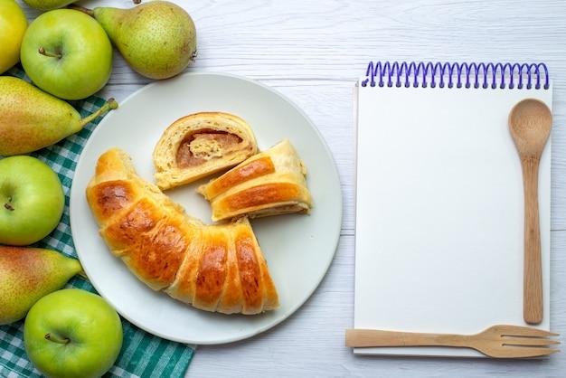 Widok z góry na upieczoną bransoletkę z pysznego ciasta uformowaną wewnątrz szklanego pokrojonego talerza wraz z notatnikiem jabłek i gruszek na białym biurku, ciastko biszkoptowe słodkie ciasteczko