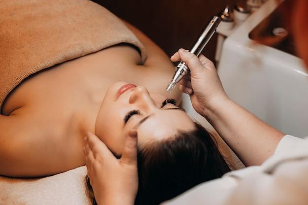 Widok z góry na uroczą brunetkę wykonującą zabieg na twarzy za pomocą fal radiowych w centrum wellness.