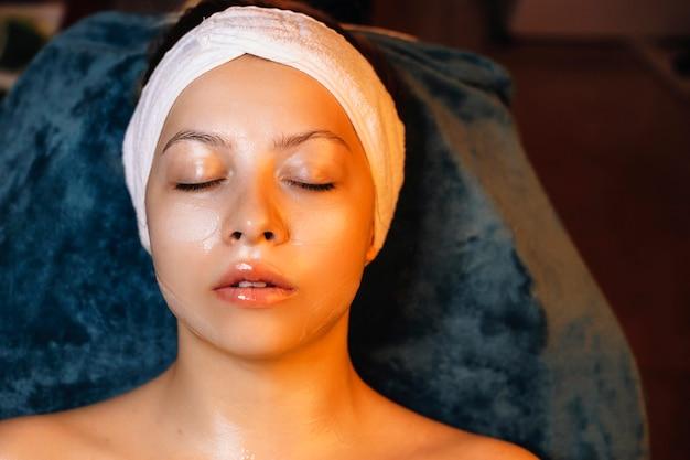 Widok z góry na uroczą kobietę opierającą się na łóżku spa z zamkniętymi oczami, relaksującą z maską z kwasem hialuronowym.
